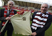 Davie (l) displays his cup final jersey on a visit to Broadwood